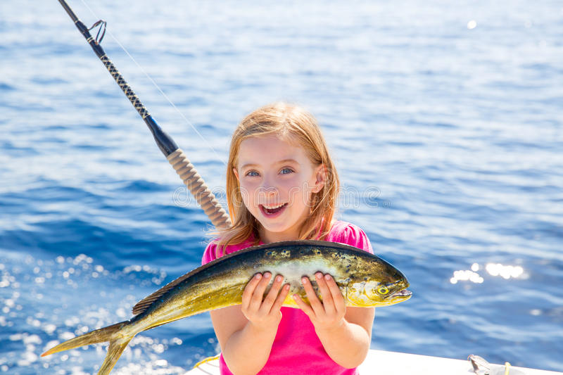 Blond kid girl fishing Dorado Mahi-mahi fish happy catch. Blond kid girl fishing Dorado Mahi-mahi fish happy with trolling catch on boat deck royalty free stock images