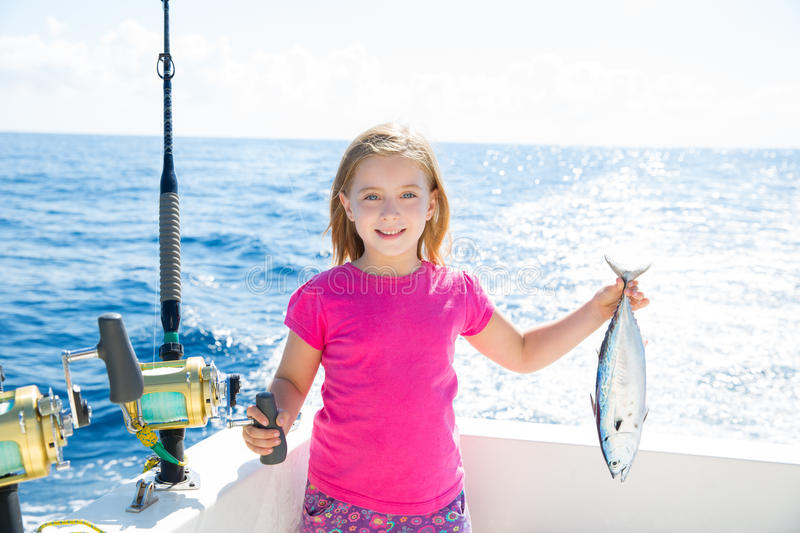 Blond kid girl fishing tuna little tunny happy with catch stock image