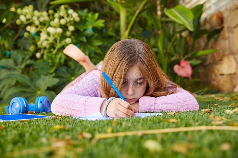 Blond kid girl homework lying on grass turf stock image