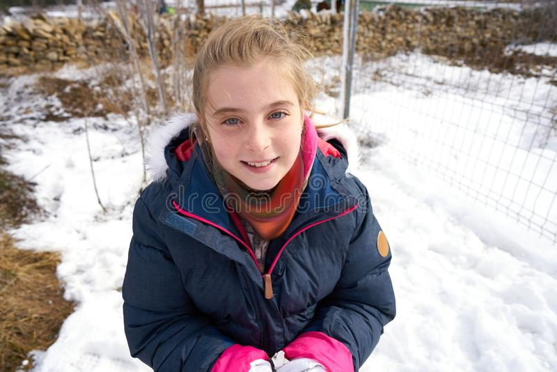 Blond girl playing with snow ball in winter royalty free stock photos