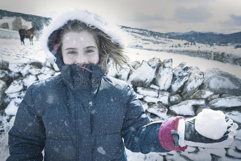 Blond girl playing with snow ball in winter stock images
