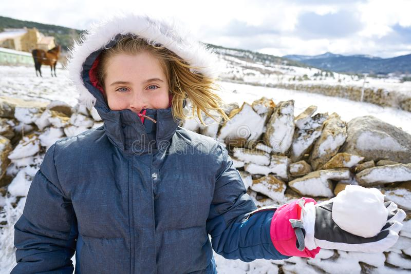 Blond girl playing with snow ball in winter royalty free stock images