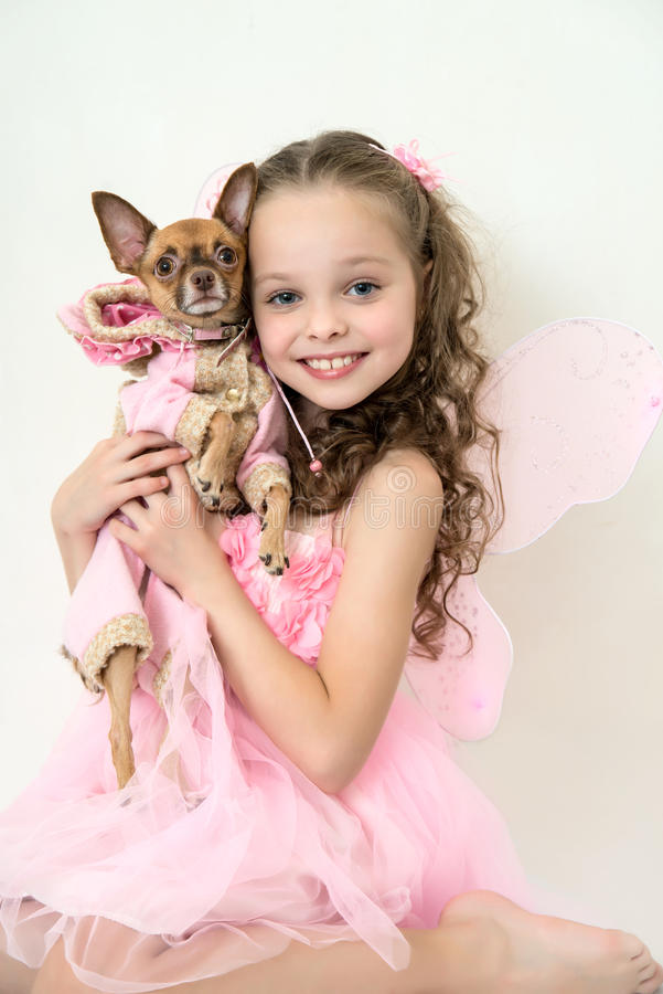 Blond kid girl with small pet dog. Blond kid girl in pink pixie dress with small pet dog royalty free stock photography