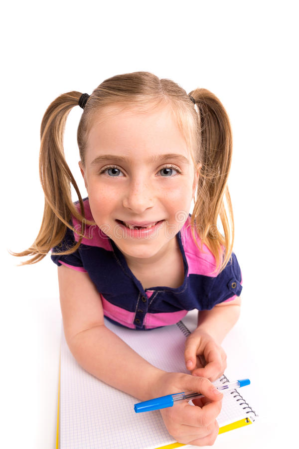 Blond kid girl student with spiral notebook in desk royalty free stock photos
