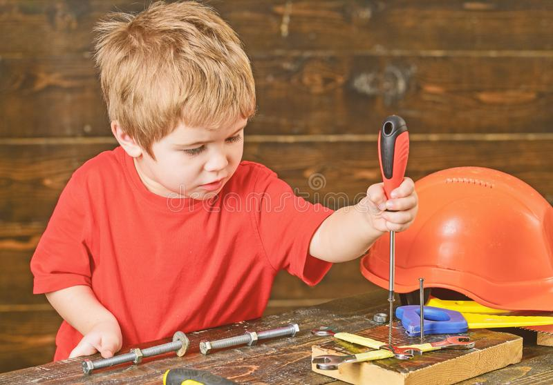 Blond kid playing in workshop. Boy binding screws to wooden board. Concentrated child learning new skills.  royalty free stock image