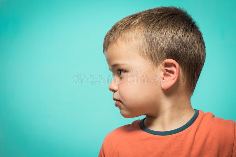 Blond kind in profiel op blauwe achtergrond royalty-vrije stock afbeelding