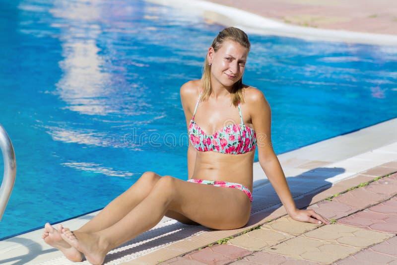 Blond kobieta cieszy się wakacje kłaść dalej sunbed w tropikalnym ogródzie obrazy royalty free