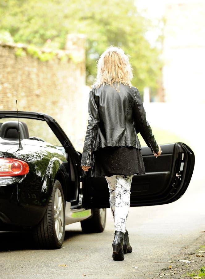 Blond kobieta dostaje w sporta samochód obraz royalty free
