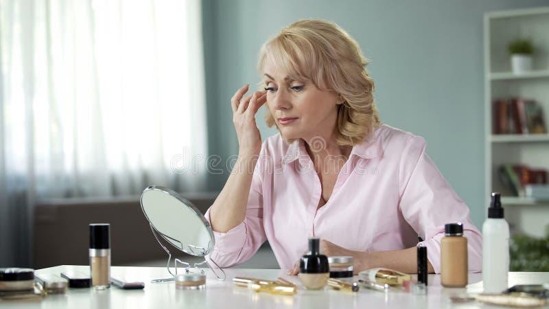 Blond kobieta patrzeje attentively w lustrze w jej 50s, zmarszczenie kosmetyki fotografia royalty free