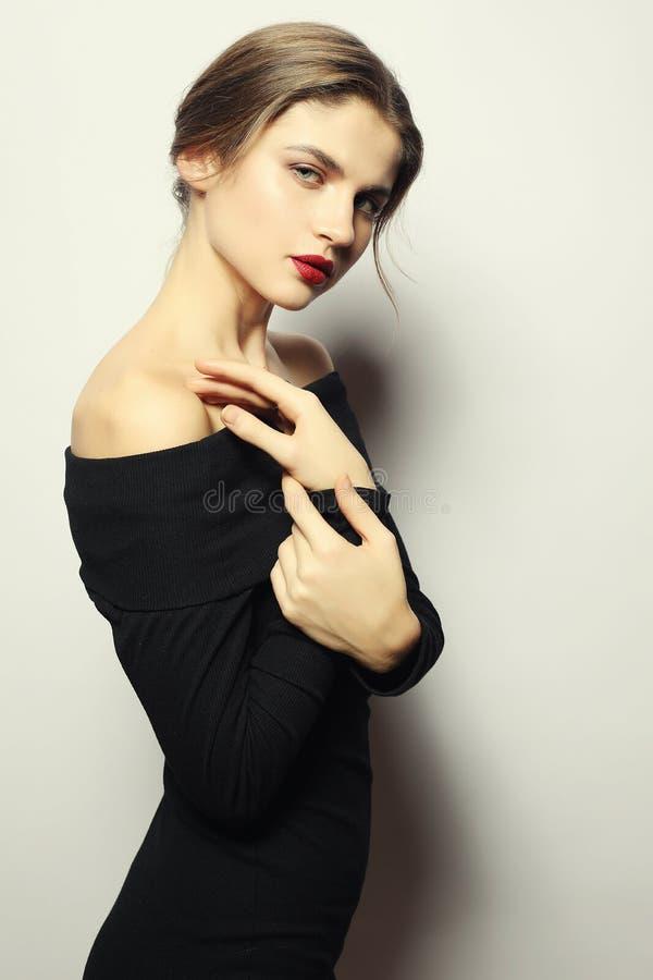 Blond kobieta w czerni smokingowy pozować z krzyżować rękami i patrzeć fotografia stock