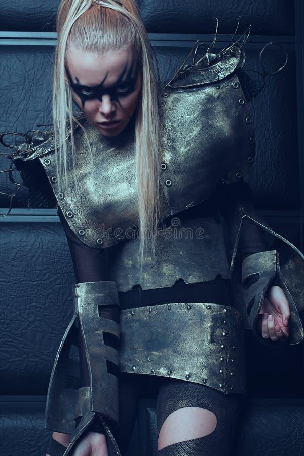Blond kobieta w stalowy opancerzenia pozować zdjęcie royalty free