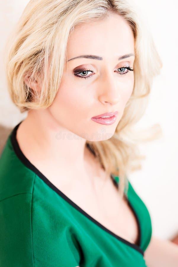 Blond kobieta w zieleni smokingowy pozować na białym zbliżeniu obrazy royalty free