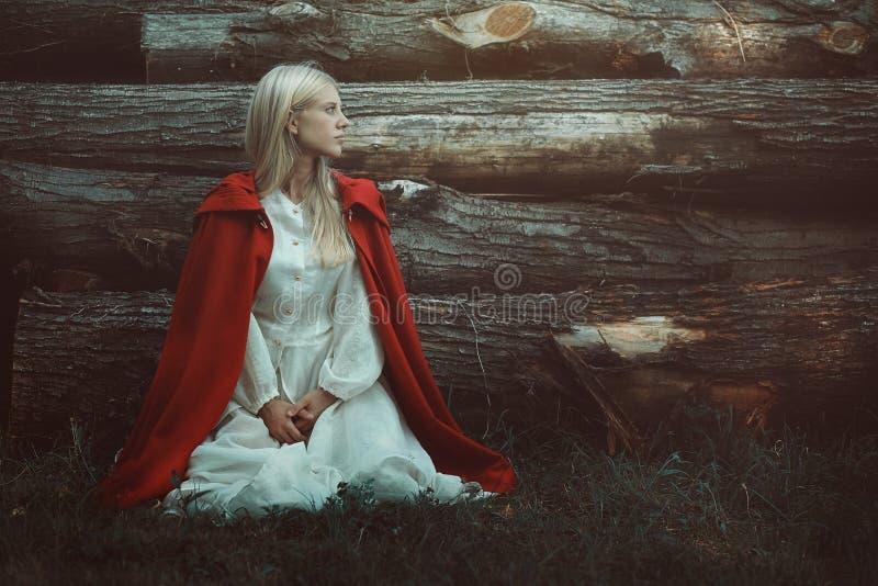 Blond kobieta z czerwieni kapturzastą peleryną zdjęcie royalty free