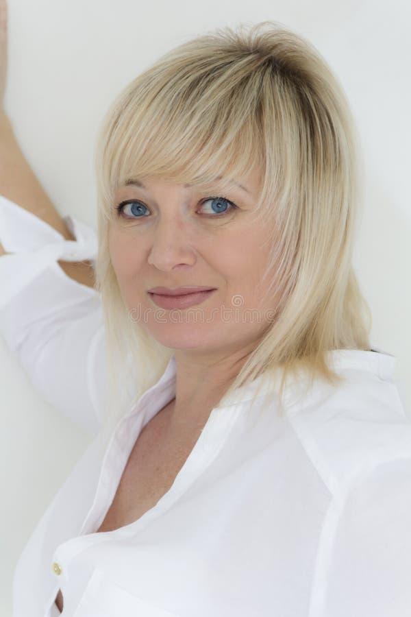 Blond kobieta z niebieskimi oczami w bielu obrazy royalty free