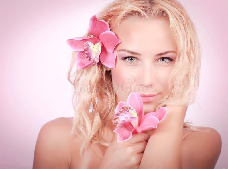 Blond kobieta z różową orchideą obrazy royalty free