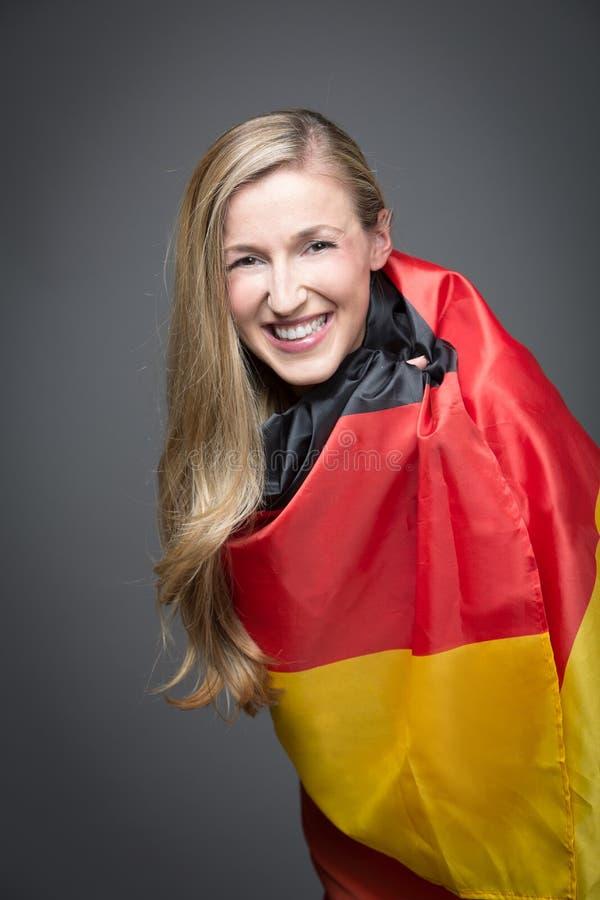 Blond kobieta zawijająca w flaga Niemcy obraz stock