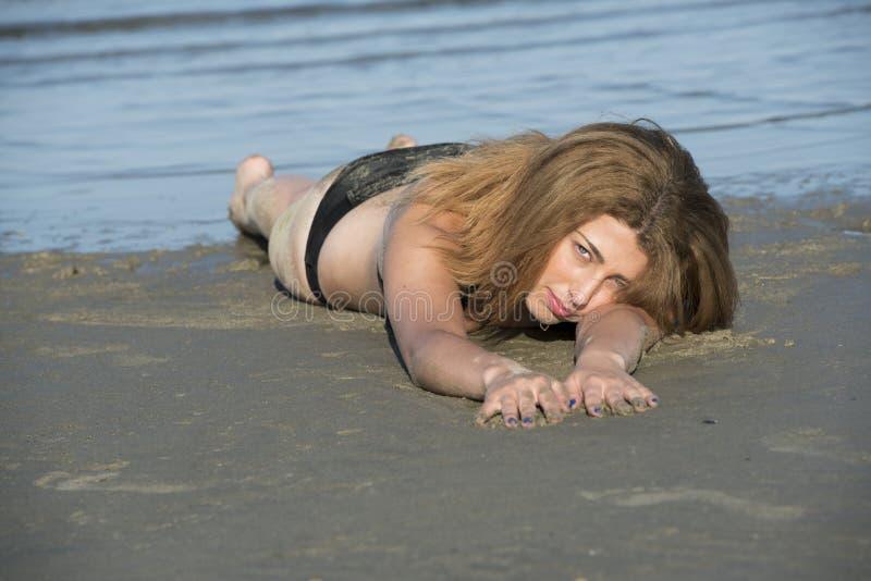 Blond kobiety odzieży czerni bikini lying on the beach na plaży zdjęcie royalty free