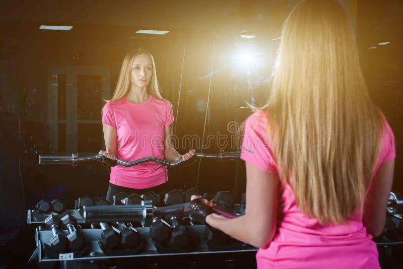 Blond konditionkvinna i sportswear med den perfekta kroppen som poserar i idrottshallen Attraktiv sportig flicka som vilar efter  arkivfoto