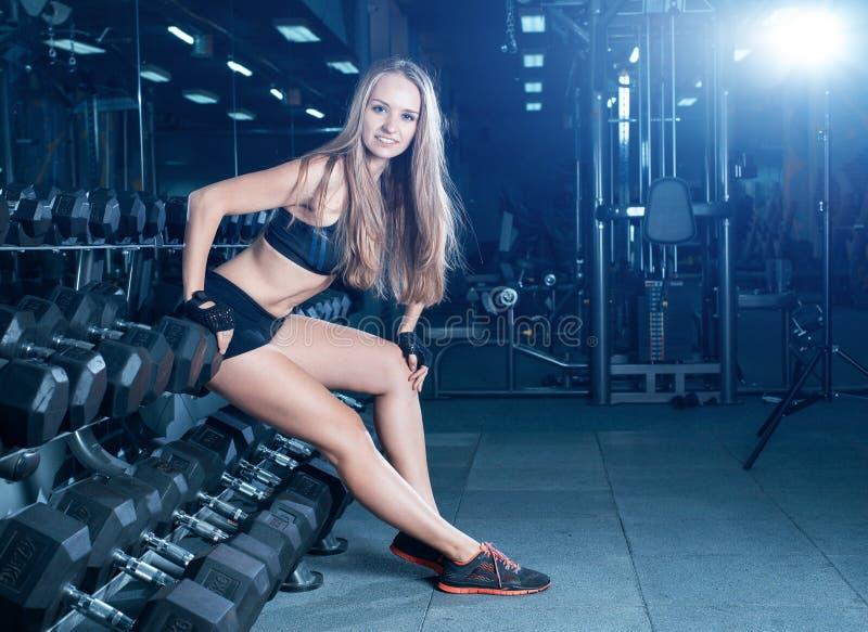 Blond konditionkvinna i sportswear med den perfekta kroppen som poserar i idrottshallen Attraktiv sportig flicka som vilar efter  royaltyfri bild