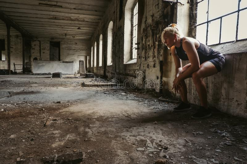 Blond konditionkvinna som vilar vid fönstret royaltyfria foton