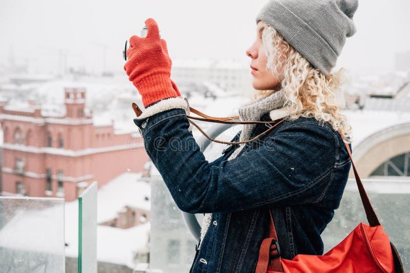 Blond krullend meisje die op de camera van de filmfoto, de winter schieten stock afbeeldingen