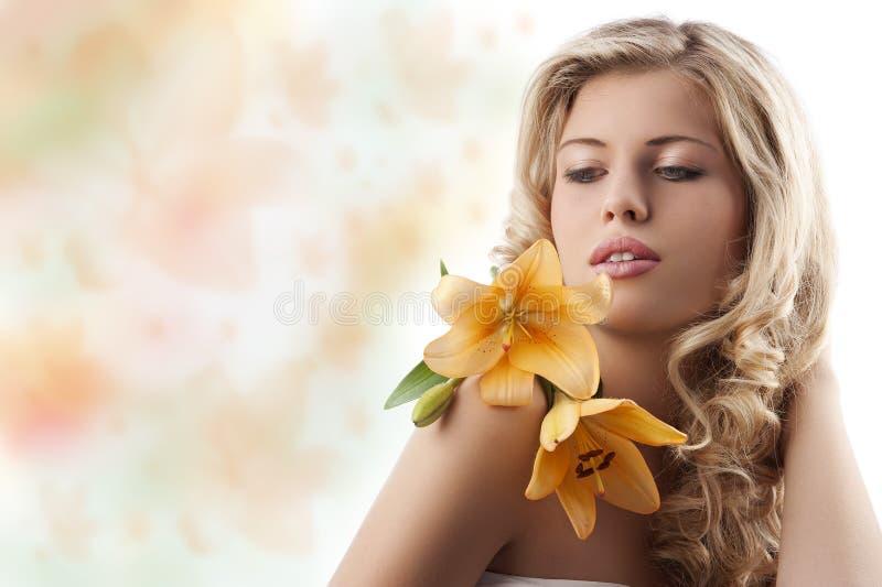 Blond krullend meisje met oranje bloem royalty-vrije stock foto's