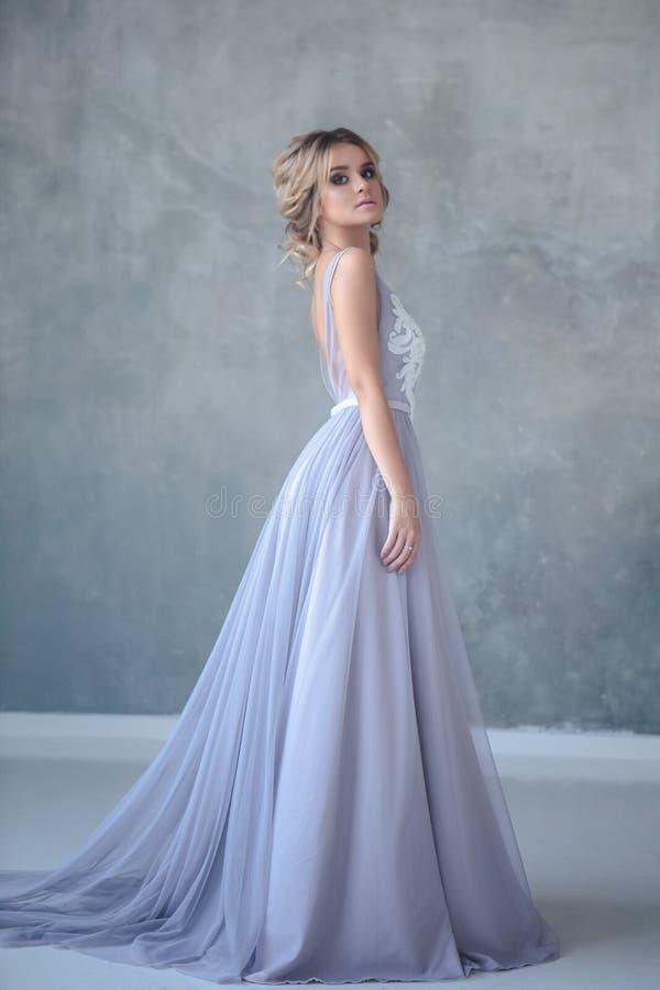 Blond kvinna för brud i en modern färgbröllopsklänning med elegant hårstil och att utgöra sexig stående för makeup för ferie för  arkivfoton