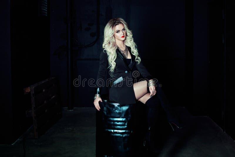 Blond kvinna för härligt mode i svart sammanträde på en metalltrumma Totalt mörk stil arkivfoton