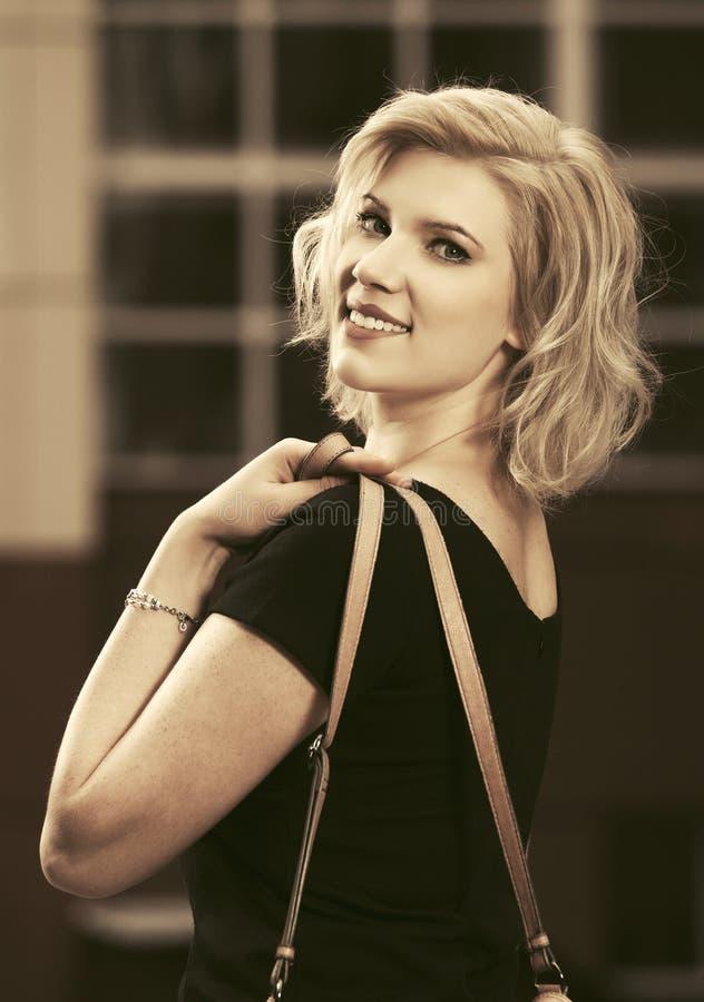 Blond kvinna för lyckligt barnmode i svart klänning som går i stadsgata arkivfoto