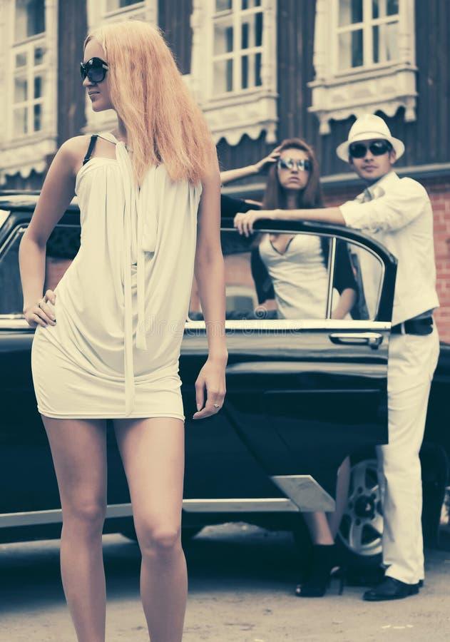 Blond kvinna för lyckligt ungt mode i solglasögon bredvid den retro bilen royaltyfri fotografi
