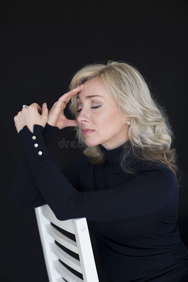 Blond kvinna för vårstående som A talar på en mobiltelefon på gatan Gå runt om stad royaltyfri foto