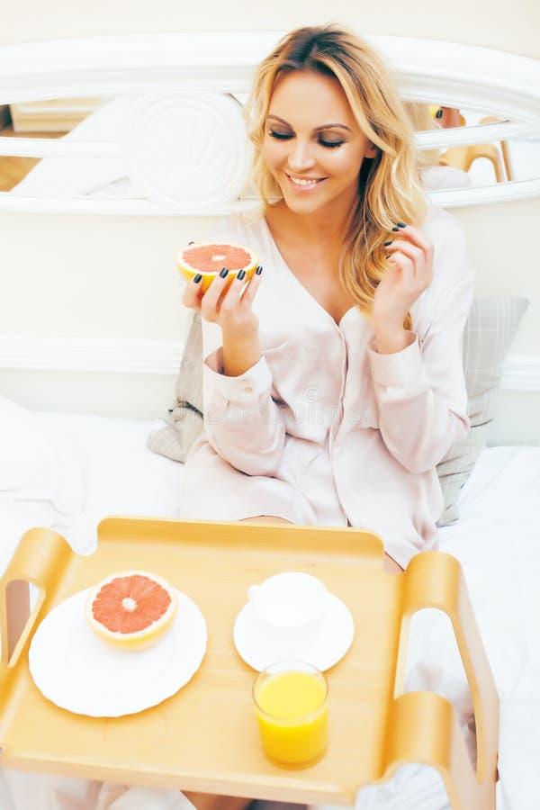 Blond kvinna f?r ung sk?nhet som har frukosten i den tidiga soliga morgonen f?r s?ng, inre rum f?r prinsessahus, sund livsstil arkivbilder