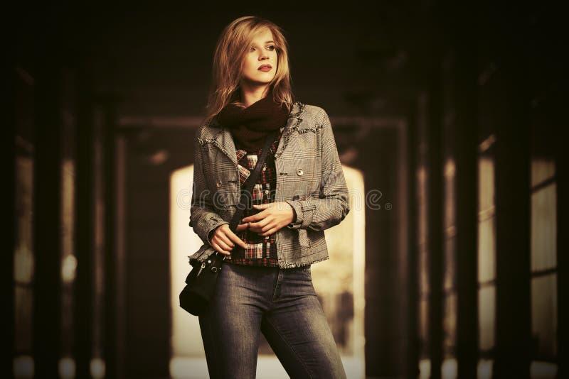 Blond kvinna f?r ungt mode som b?r den kontrollerade pl?dblazer p? stadsgatan royaltyfri foto