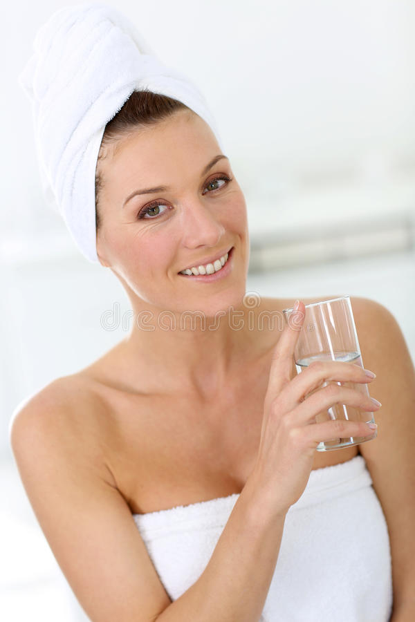 Blond kvinna i badrumdricksvatten royaltyfri foto