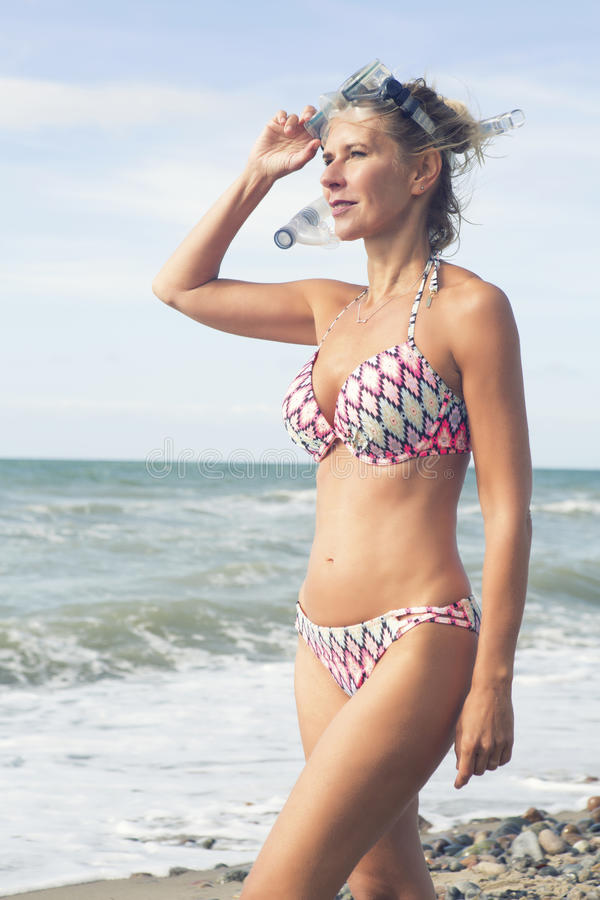 Blond kvinna i bikini på stranden royaltyfri fotografi