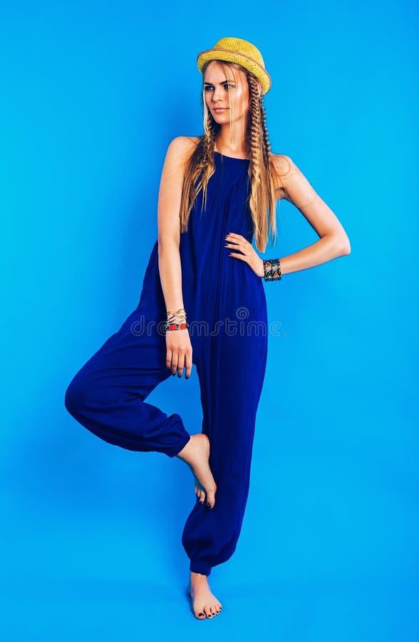Blond kvinna i blå overall- och sugrörhatt royaltyfria bilder