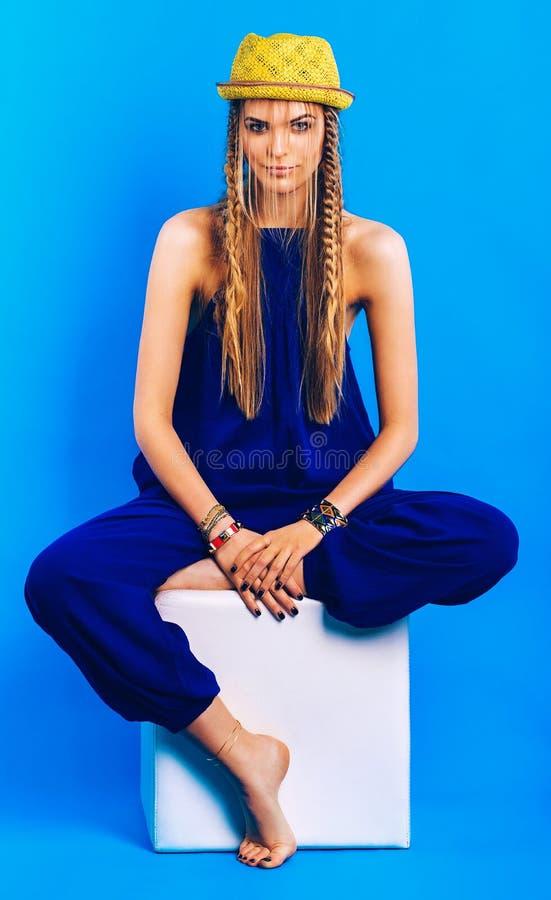Blond kvinna i blått overall- och hattsammanträde på stol arkivfoto