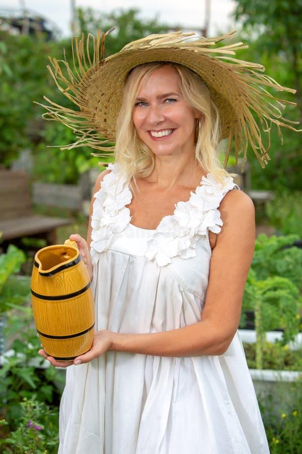 Blond kvinna i den vita klänningen som bevattnar blommor i trädgården arkivbilder