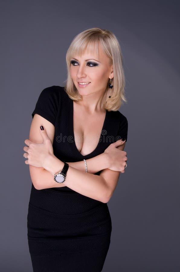 Blond kvinna i en åtsmitande klänning arkivfoto