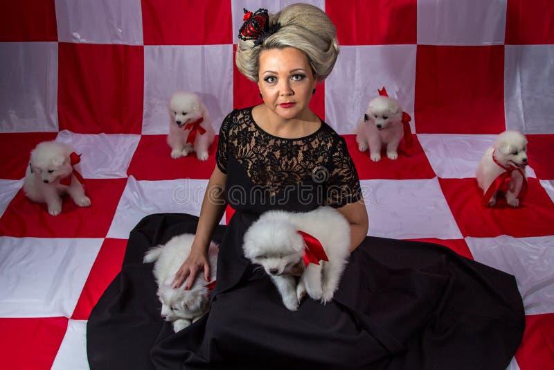 Blond kvinna i krona med vita valpar arkivfoto