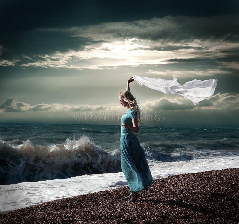 Blond kvinna i lång klänning på det stormiga havet arkivfoton