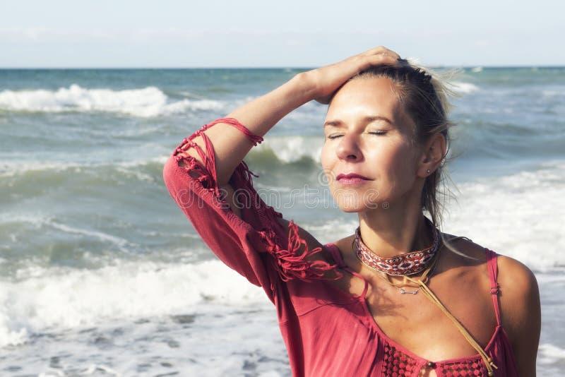 Blond kvinna i rött klänninganseende vid havet arkivfoto