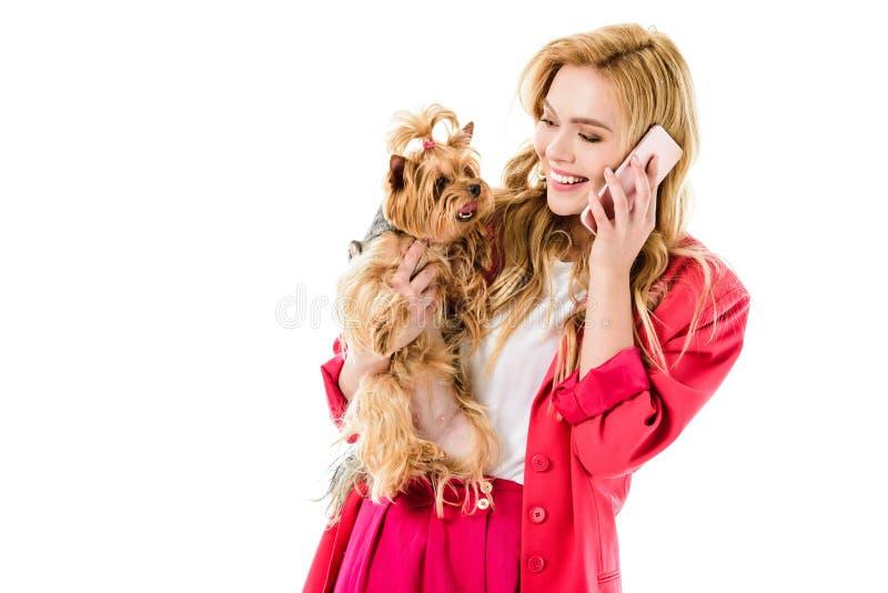 Blond kvinna i rosa kläder som talar på telefonen och rymmer den gulliga hunden arkivfoto