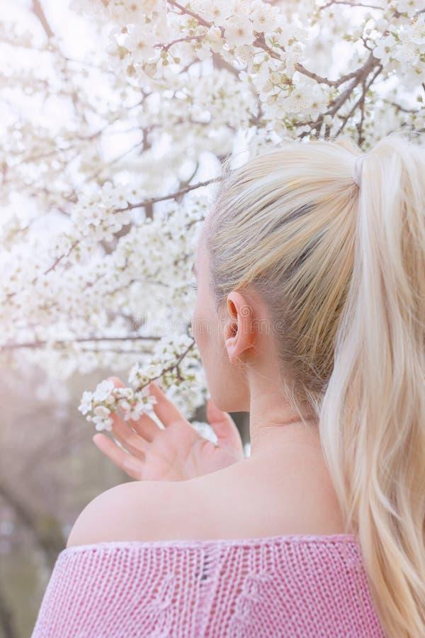 Blond kvinna i rosa tröja, med blont hår i hästsvans, hand som trycker på vita blommor royaltyfri foto