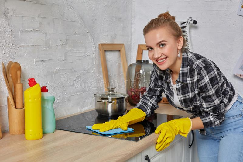 Blond kvinna i skyddande handskar med trasan som gör ren hemmastatt kök för elektrisk ugn Flicka som tvättar svart skinande ytter royaltyfri bild