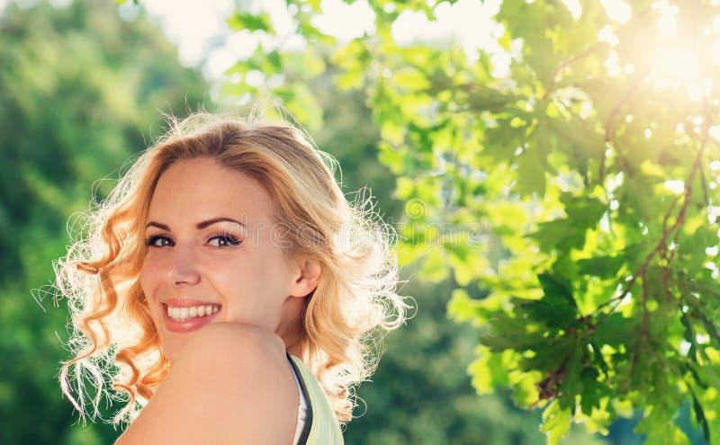Blond kvinna, lockigt hår i grön natur solig sommar royaltyfria foton
