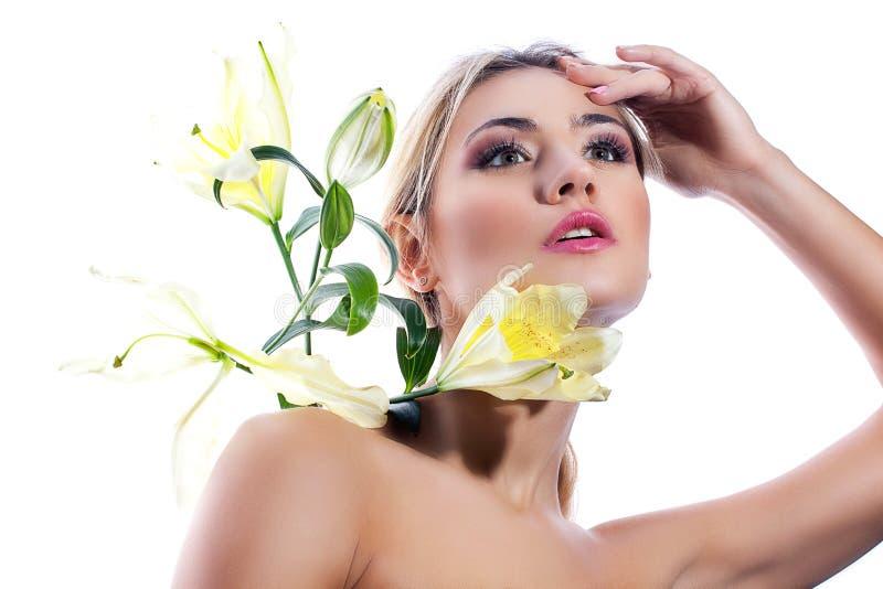 Blond kvinna med den isolerade nya rena blomman för för hud och vit lilja arkivbilder