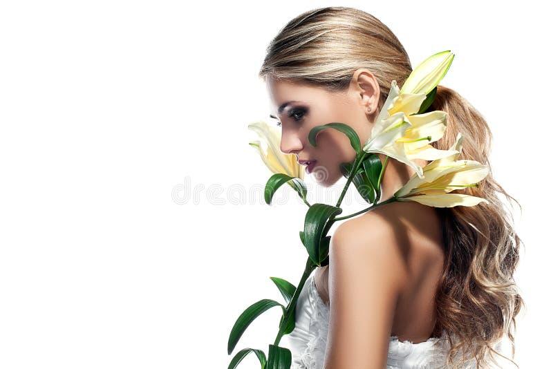 Blond kvinna med den isolerade nya rena blomman för för hud och vit lilja arkivfoton