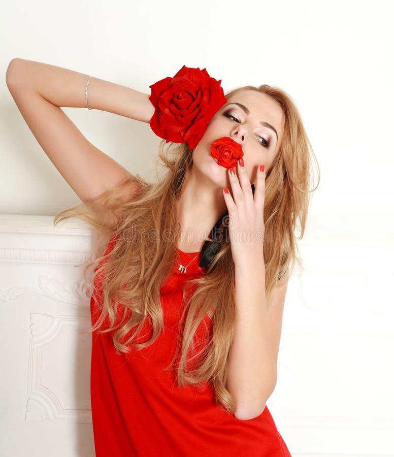 Blond kvinna med den röda rosen i studio, flicka och blomma royaltyfri fotografi