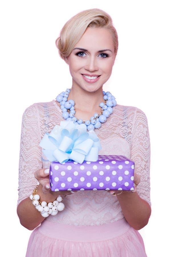 Blond kvinna med det härliga leendet som ger den färgrika gåvaasken Jul ferie arkivfoto